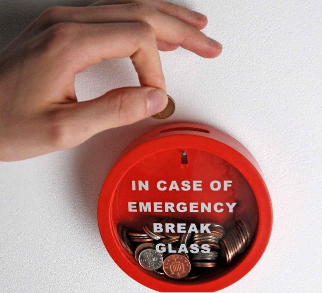 Coins in a container with label: 'In case of emergency break glass'.