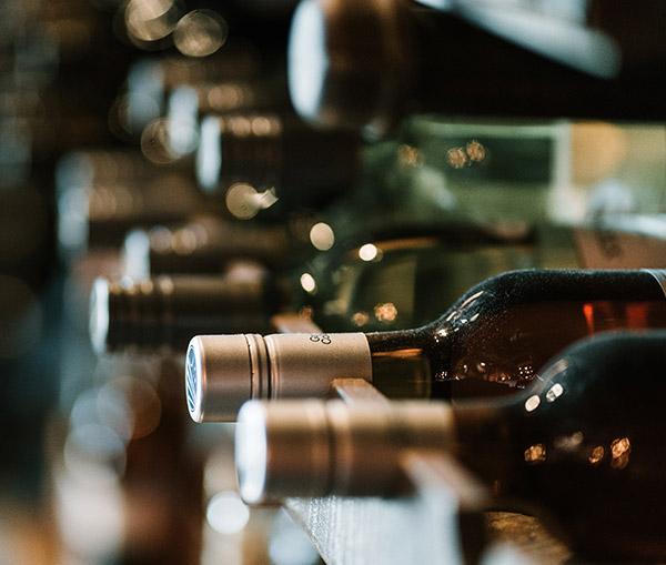 Variety of wine bottles on a shelf in a wine cellar.